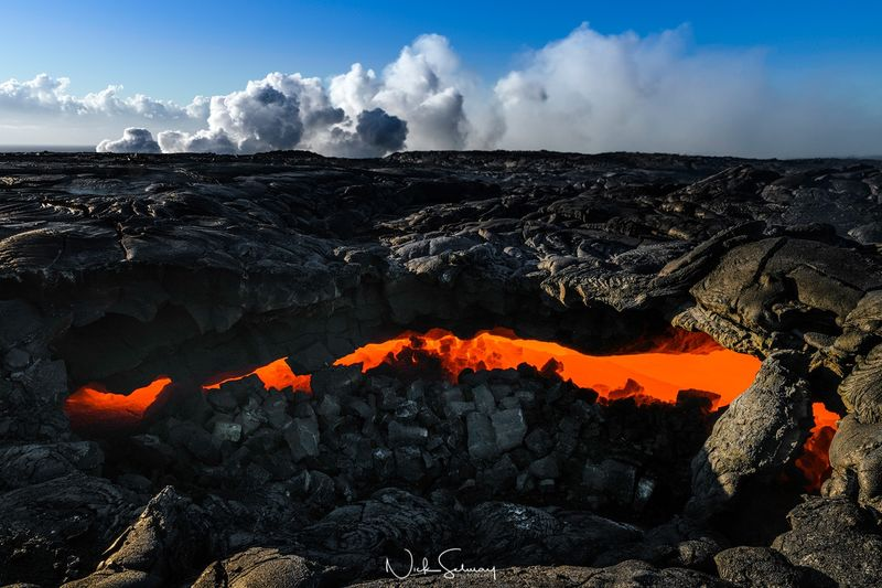 In this image of flowing lava, a lava channel runs boldly under the charred ground. Shop this print & a variety of channels of lava underground images for sale.