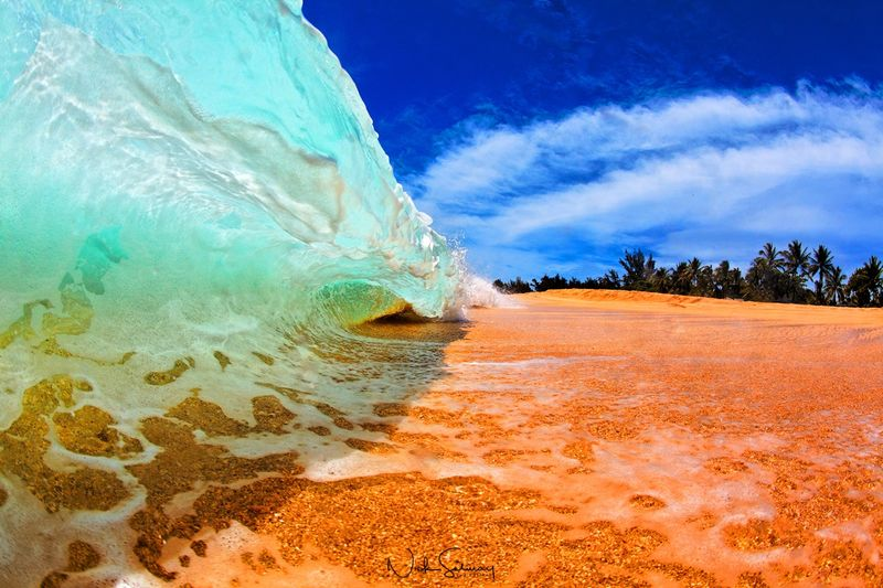 In this beautiful photo, a small wave crashes into the shore in Keiki Beach in Oahu. Shop this print & a variety of Hawaii shorebreak photography for sale.