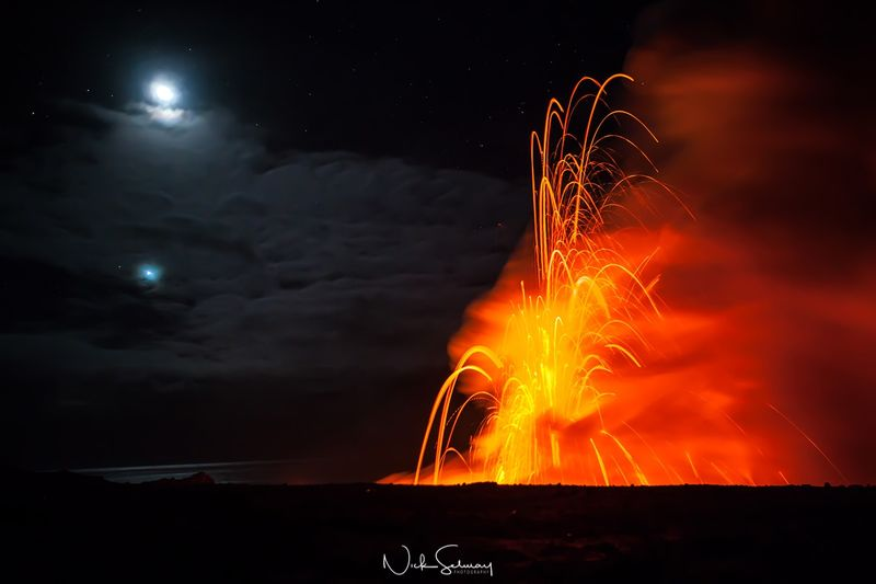 In this moonlit image, lava explodes from a volcano standing out vibrantly from the night sky. Shop this print & a variety of photos of volcanos & lava for sale