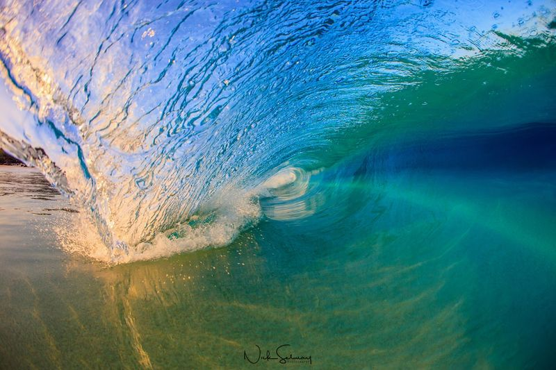 In this photo of a big wave in Hawaii, a smooth and serene wave rolls in the ocean gracefully. Shop this print & a variety of big wave photography in Hawaii.