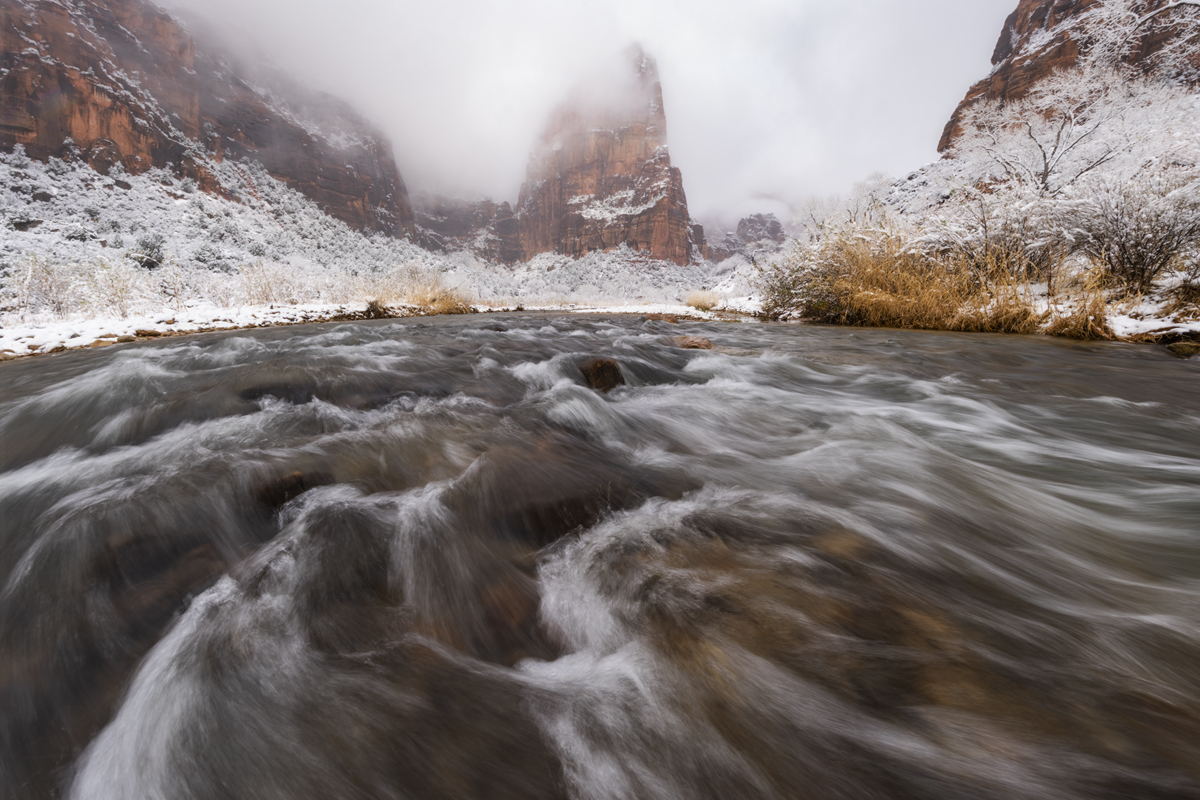 Early morning snow storm covers the red rock wall of Zion National Park with the Virgin River flowing and Angels Landing in the...