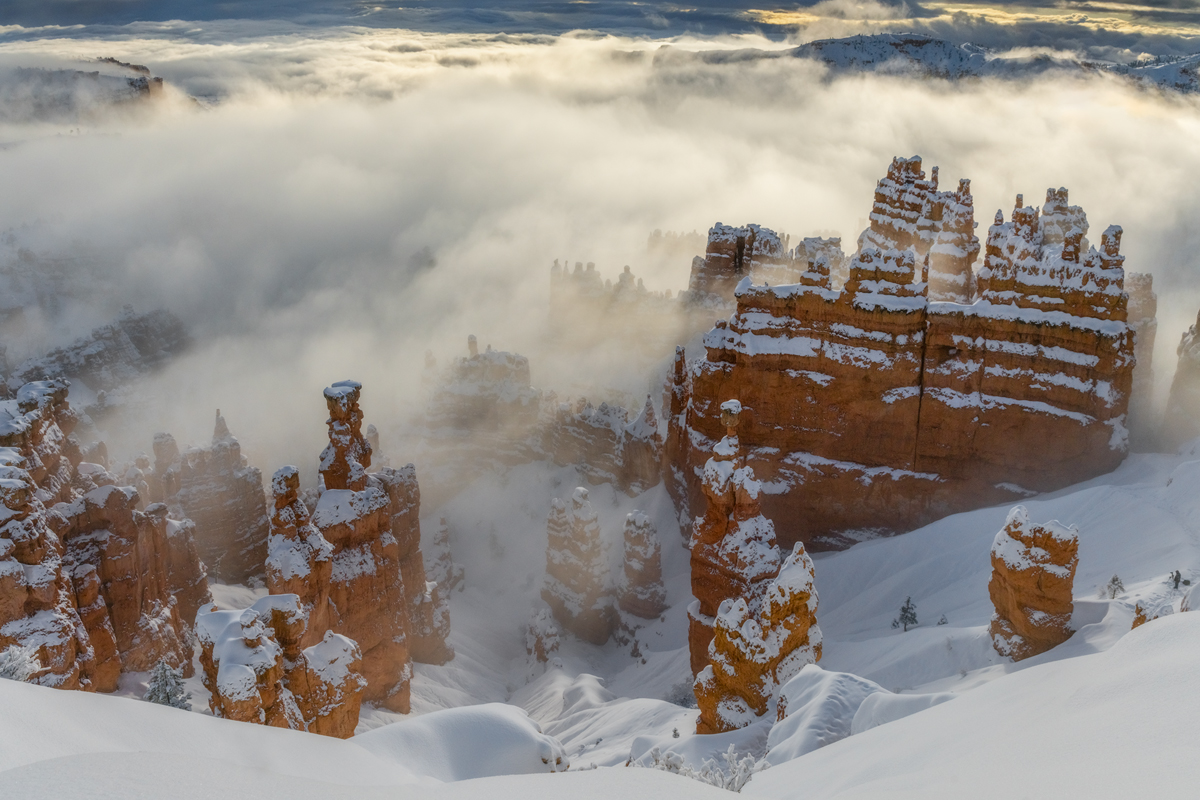"""Fog and sunrise light drift in and out surrounding the famous """"Thors Hammer"""" in Bryce Canyon an other worldly rock formation."""