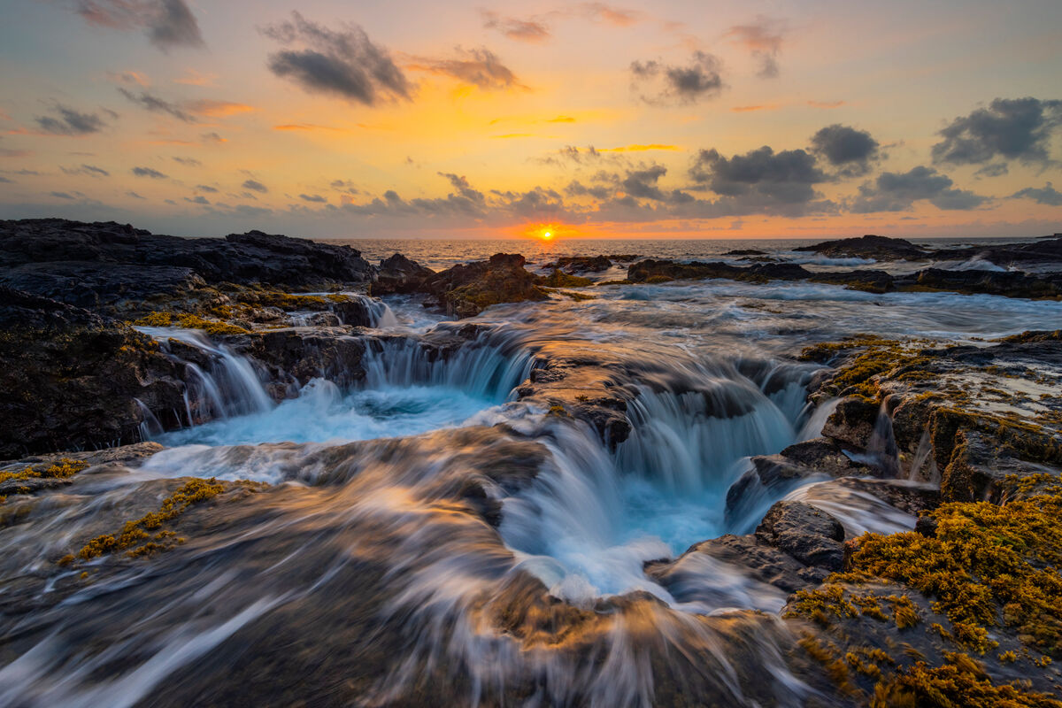 Waves crash against the rugged coast of the Western Side of the Big Island then draining back in to the huge holes making for...