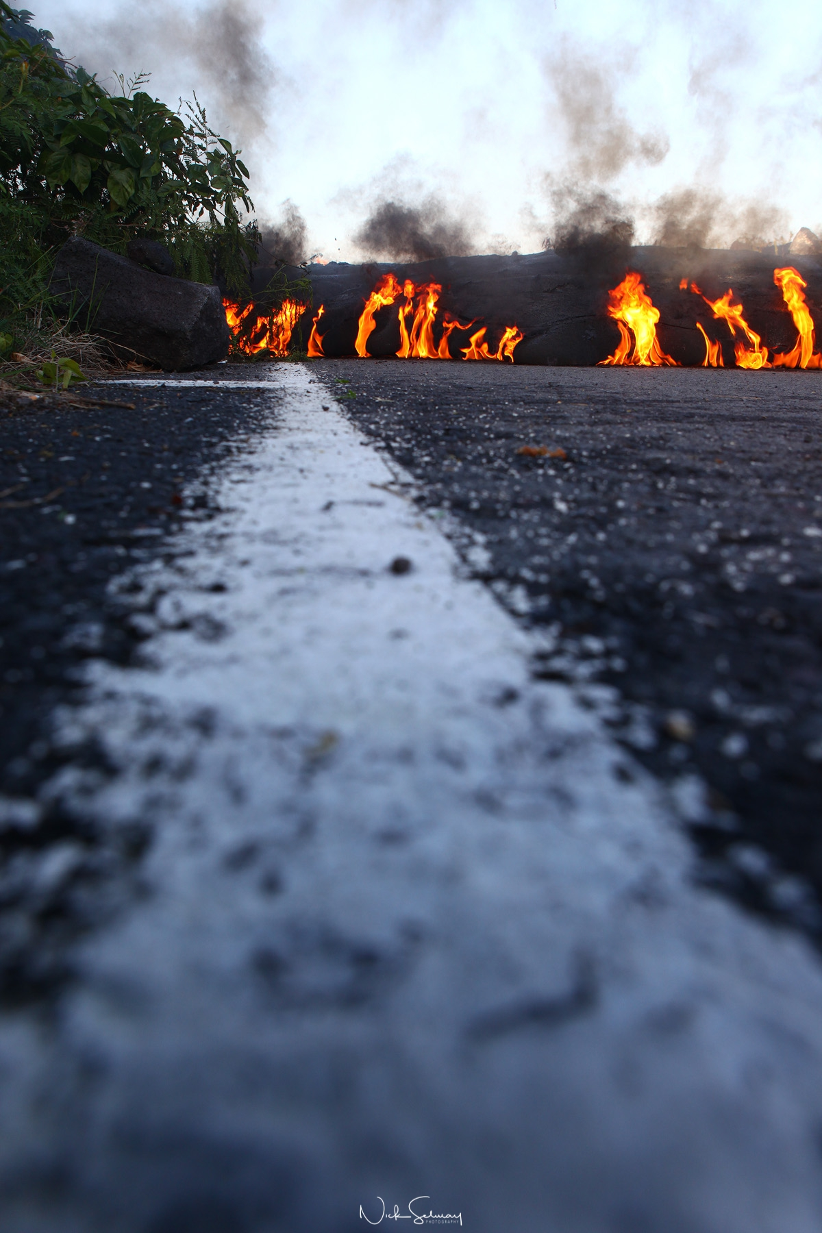 In this image of hot lava, lava burns a road on the edge of Volcano National Park in HI. Shop this print & a variety of hot lava photography for sale.
