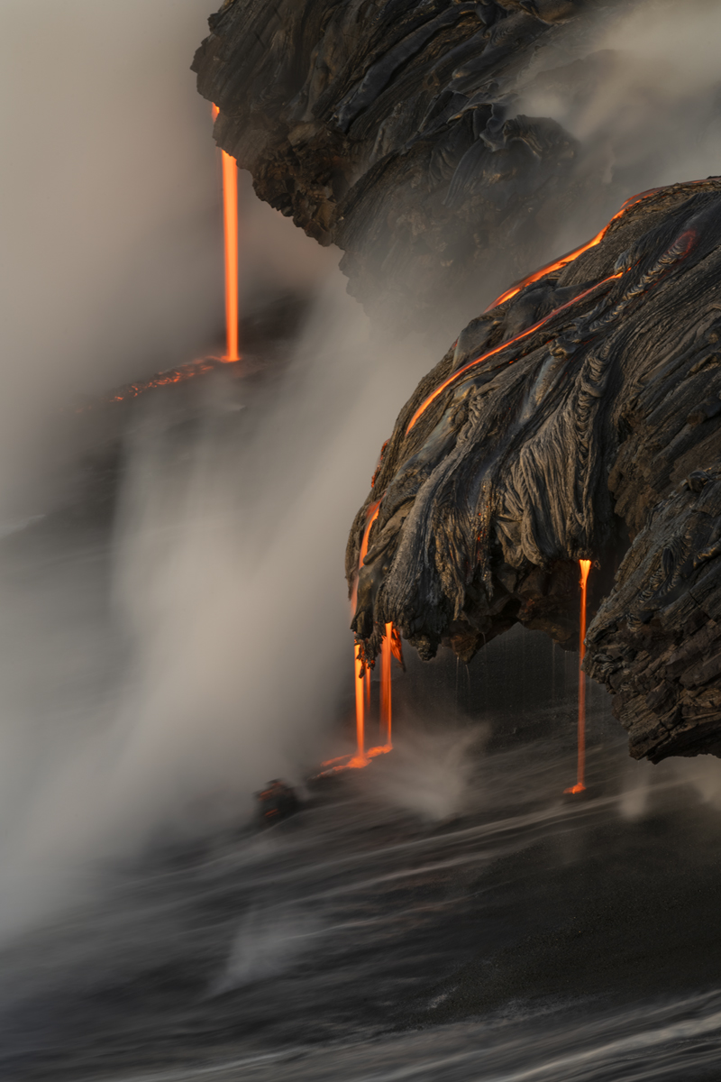 3 Drips of lava enter the ocean onto a new black sand beach just at the first light of sunrise.