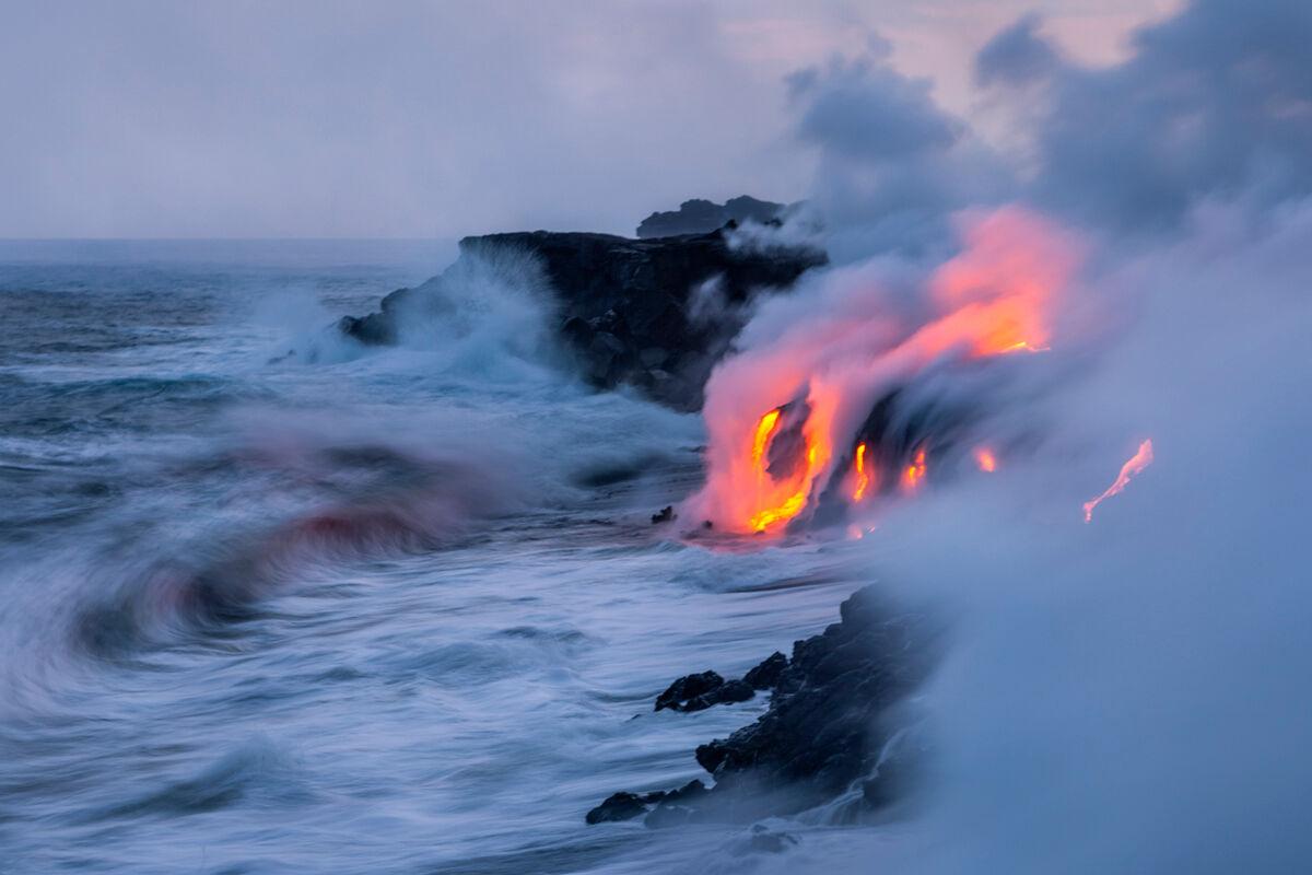 A shore break waves curls toward the lava ocean entry.