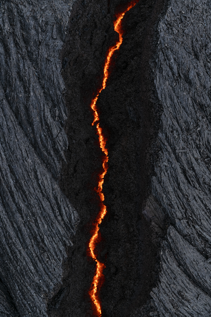 A small glow of lava peaking through a crack in the ground.