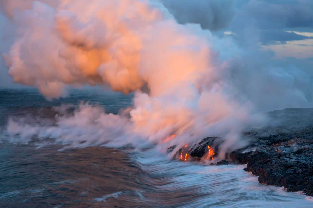 Pink sunrise light gives color to the steam plume with the glow of the lava below.