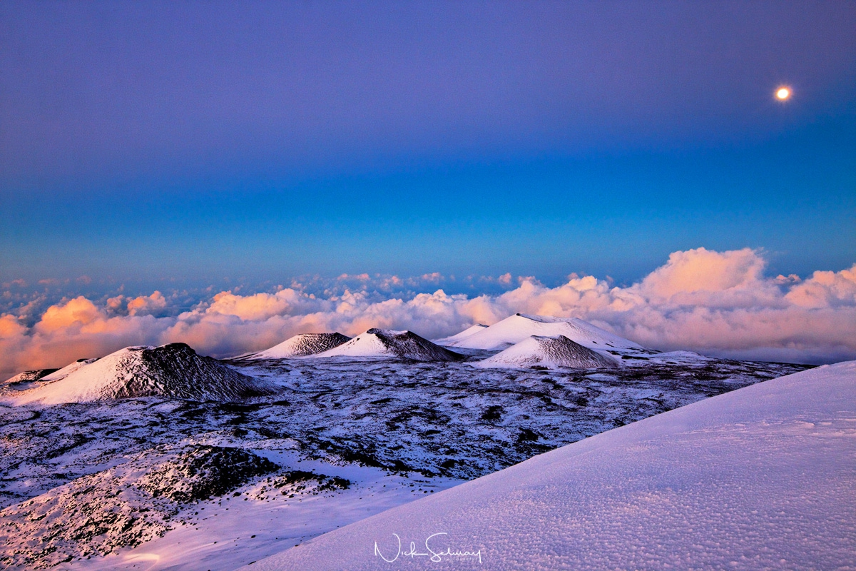 The moon rise over the snow covered craters along the side of Mauna Kea.