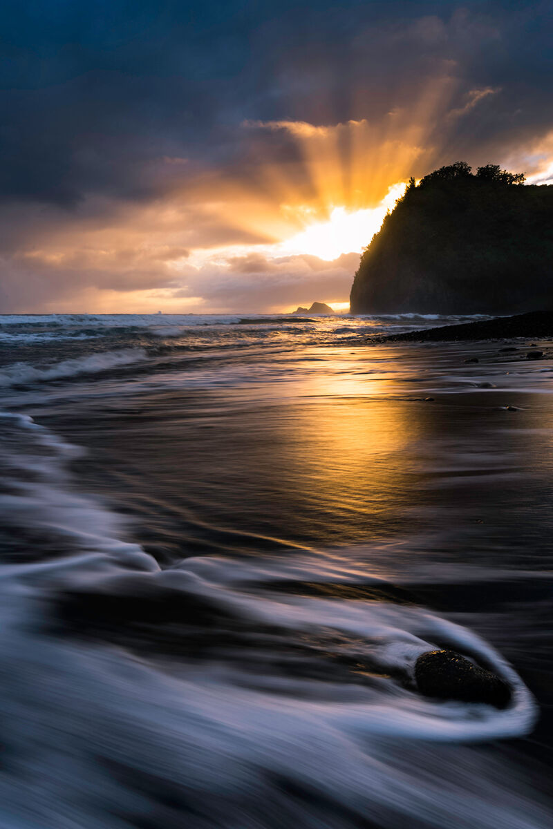 Just as the sun came up the light exploded through the clouds reflecting the warm light across the black sand beach of Pololu...
