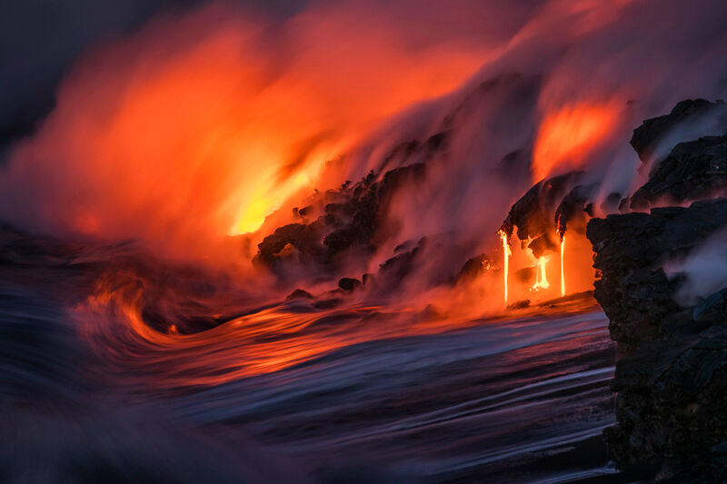 Lava pours into the Pacific Ocean as the waves crash against it.