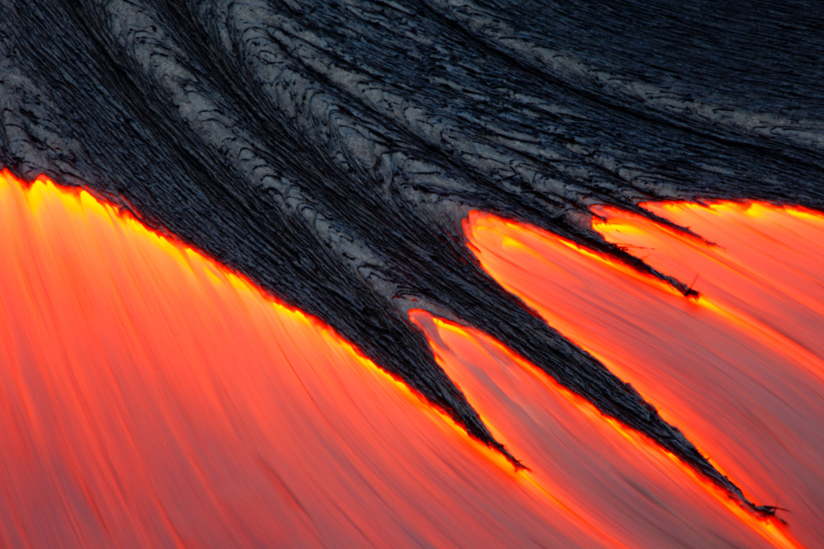A simple yet powerful image of the lava flowing out of a crack on the surface of the ground.