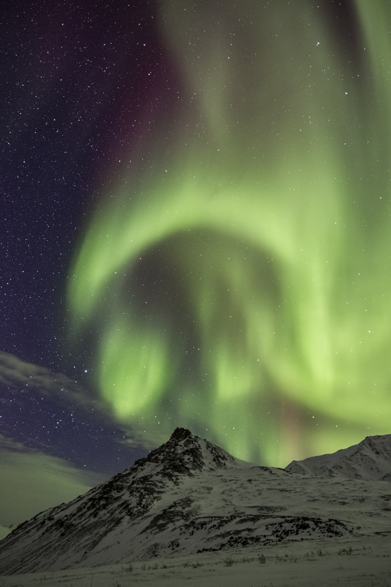 A unique formation of Northern Lights form over a loan mountain peak in The Brooks Range,Alaska.