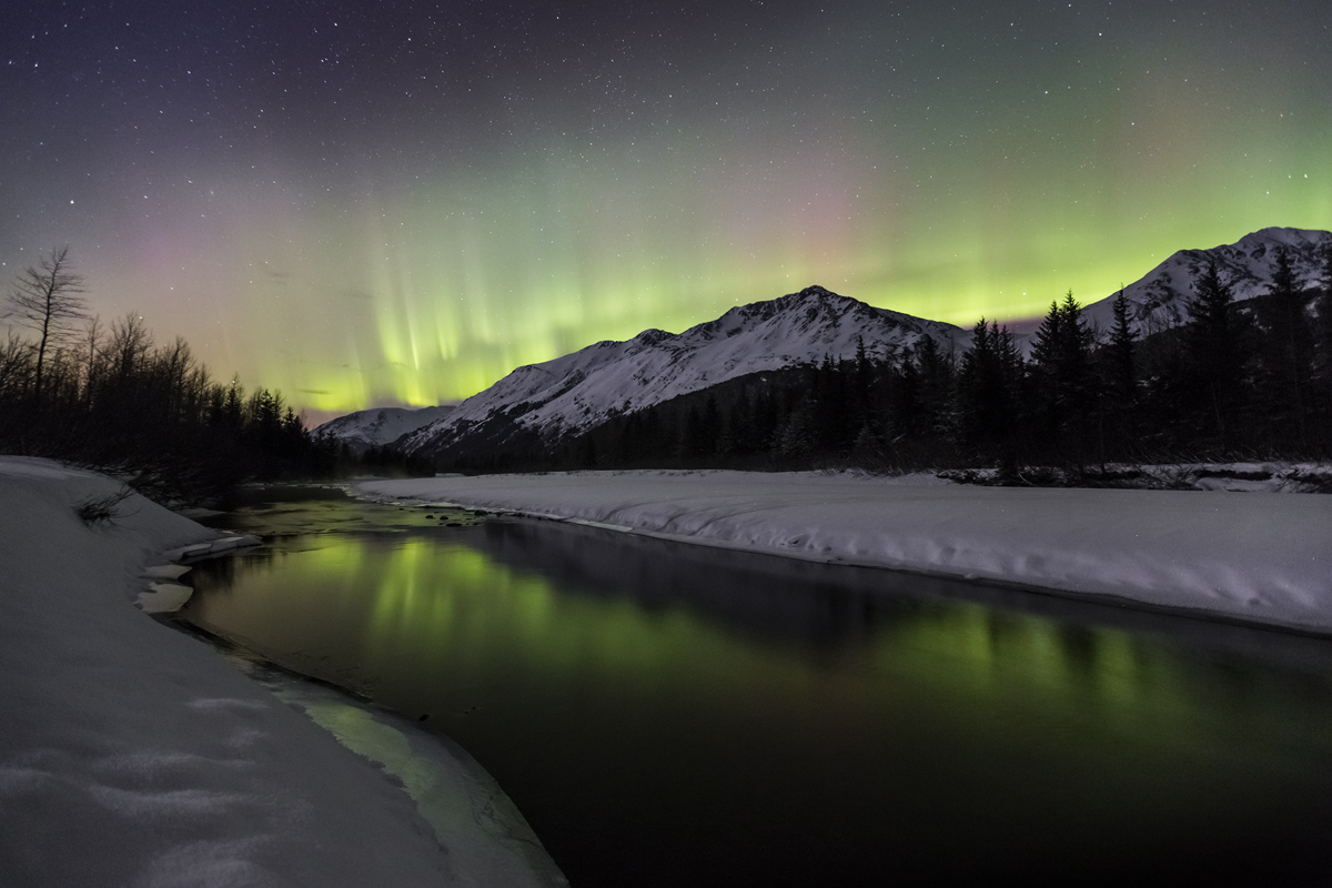 A perfect reflection of northern lights on a small river as they dance in the night sky.